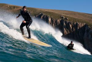 Surfar no inverno: Homem pegando onda com neoprene de manga longa e touca