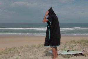 Surfar no inverno: Homem de poncho de surf na areia da praia