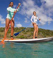 Duas mulheres praticam SUP com roupas dom proteção solar