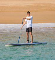Homem praticando SUP perto da costa num dia ensolarado
