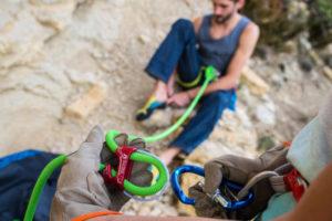 homem calçando a sapatilha de escalada se preparando para escalar