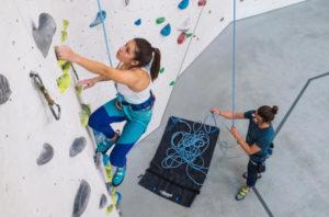 Mulher subindo uma parede de escalada em ginásio indoor com sua corda de segurança