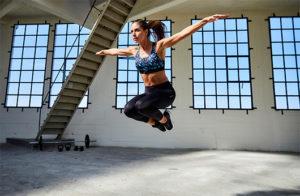 Mulher fazendo exercícios de saltos com top esportivo que ajuda manter os seios firmes