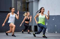 Grupo de três mulheres fazendo circuito de exercícios sem equipamentos