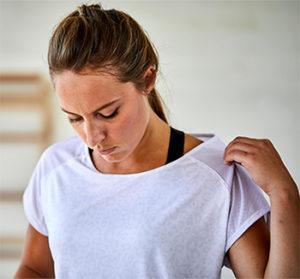 Musa fitness ajeitando sua camiseta branca antes de começar seu treino cardio