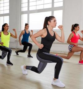 Grupo de mulheres fazendo exercício que simula subir escada