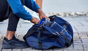 Homem colocando material esportivo na mala que está no chão