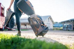 Uma praticante e fã de hipismo andando e puxando sua mala de rodinhas