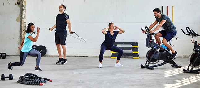 Grupo de adultos praticando Ciruito de exercícios físicos de treino cardio