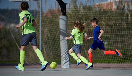 Crianças jogando futebol em quadra poliesportiva durante o dia
